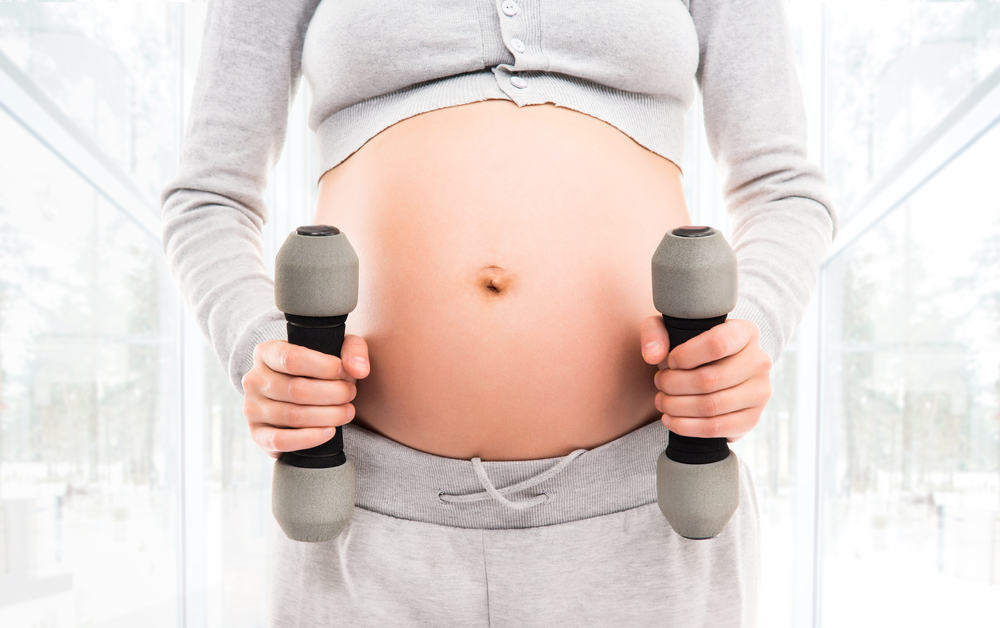 Pregnant mother in 3rd trimester working out with dumbbells.