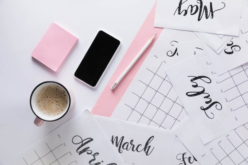 desk with calendars on them and a smartphone and pink desk supplies