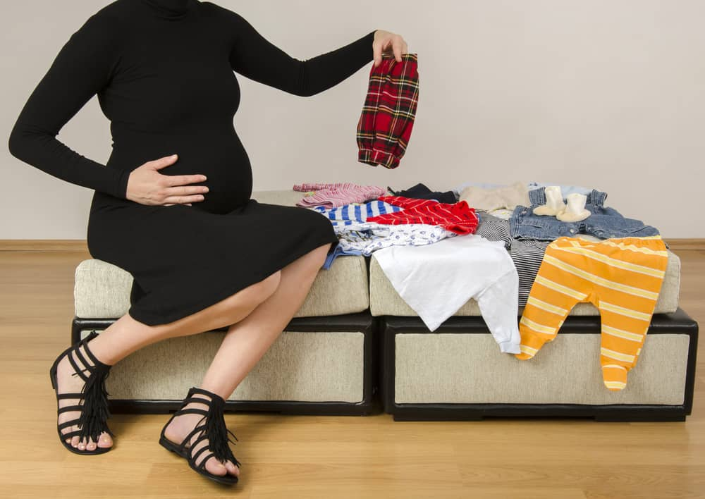 pregnant lady sitting on furniture holding baby clothes from a pile of baby clothes sitting on baby nursery furniture