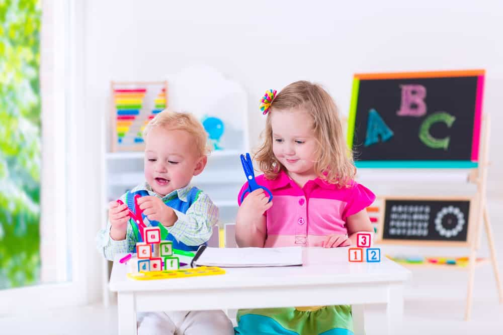 Kids learning with scissors in a preschool environment.
