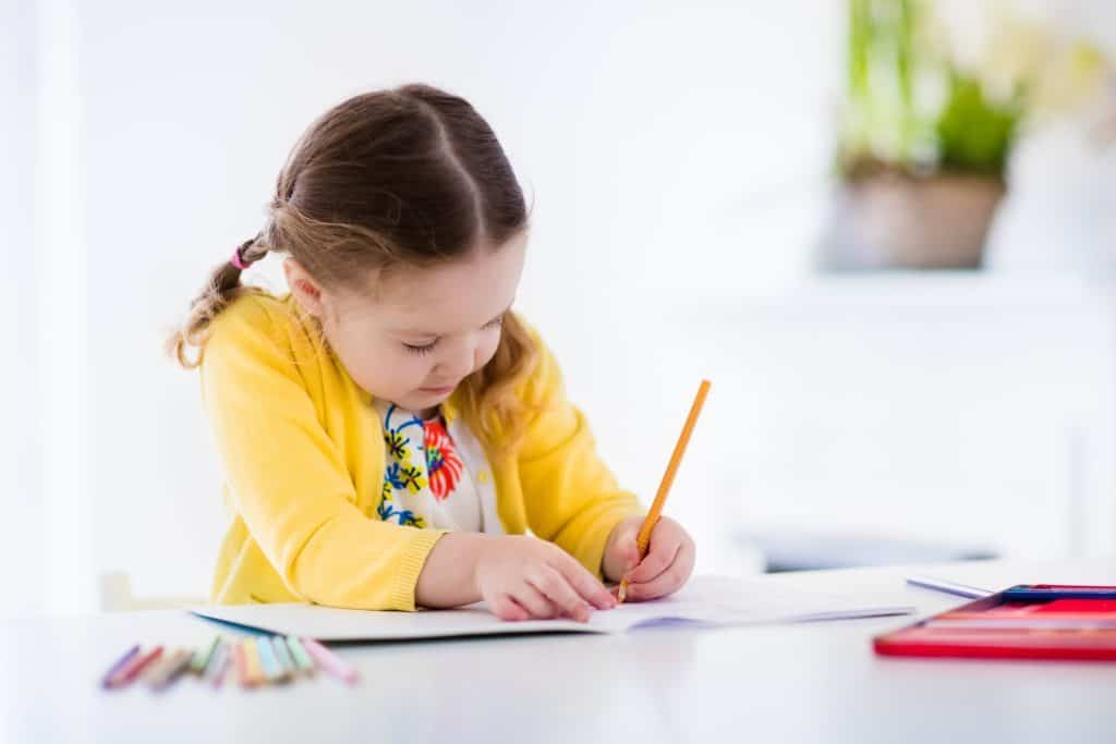 toddler practicing writing skills with pencil.