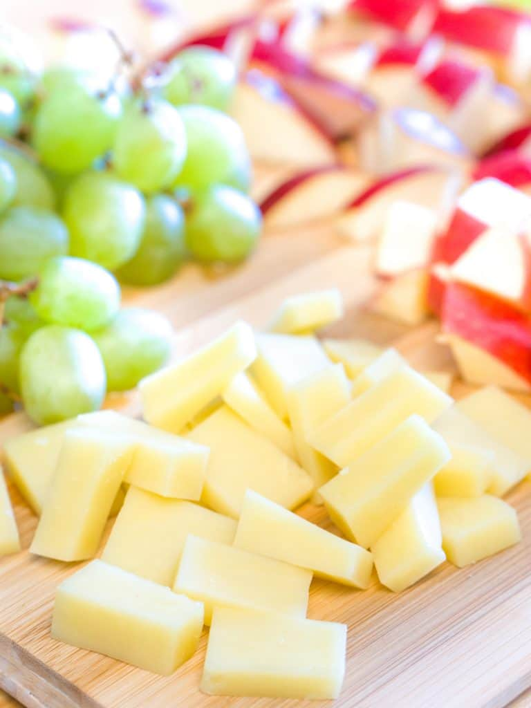 Close up photograph of a bamboo wood cutting board with an appetizer spread including cheese, green grapes and pieces of apple sliced up.