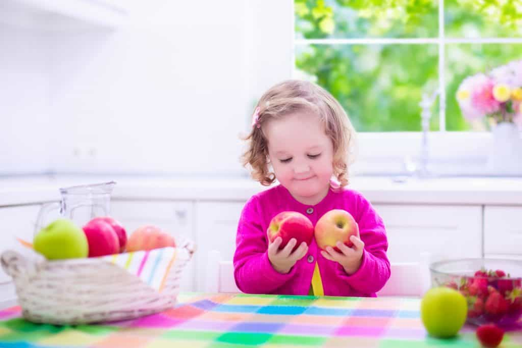 Child eating breakfast. Kids eat in a white kitchen. Children having fresh fruit. Little kid playing peek a boo with apples. Cute preschooler girl with apple and strawberry on a sunny morning. Healthy nutrition for toddlers.