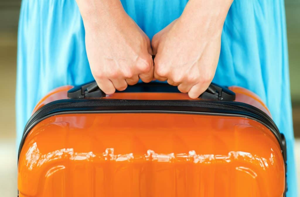 a lady in a blue dress holding an orange suitcase waiting to get on her cruise with her packed luggage.