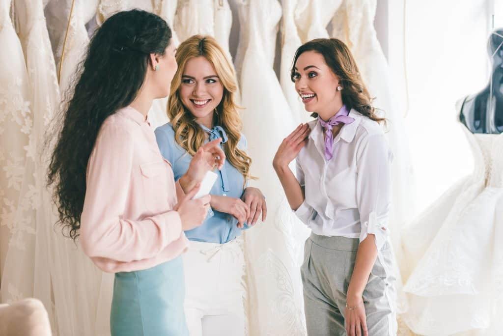 friends talking in front of wedding dresses.