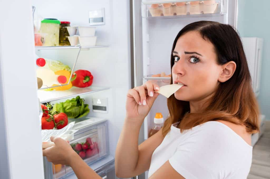 Lady eating cheese in front of open refrigerator.