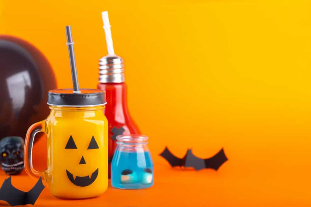 Halloween healthy pumpkin or carrot drinks in the glass jar on a orange background with copy space