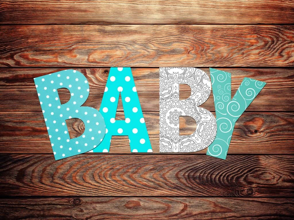 letter to spell baby on wooden floor.