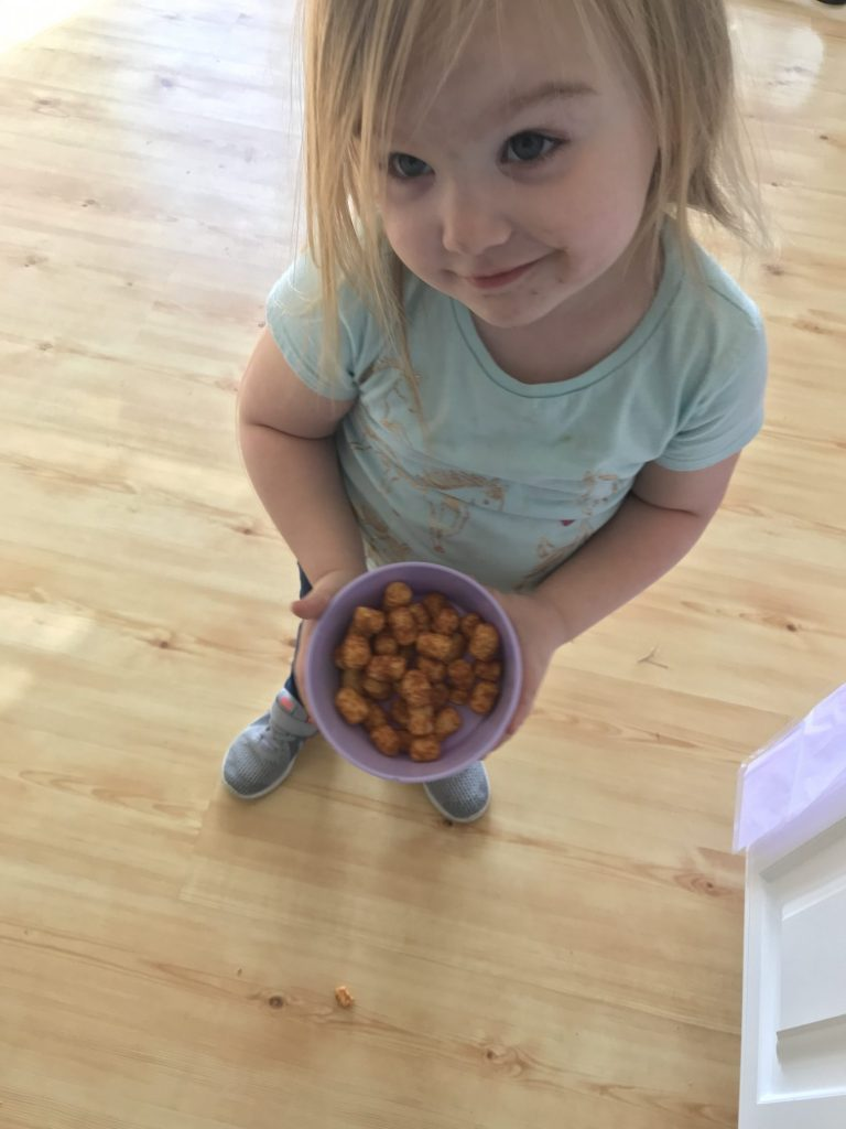 daughter with peanut butter puffs in a bowl