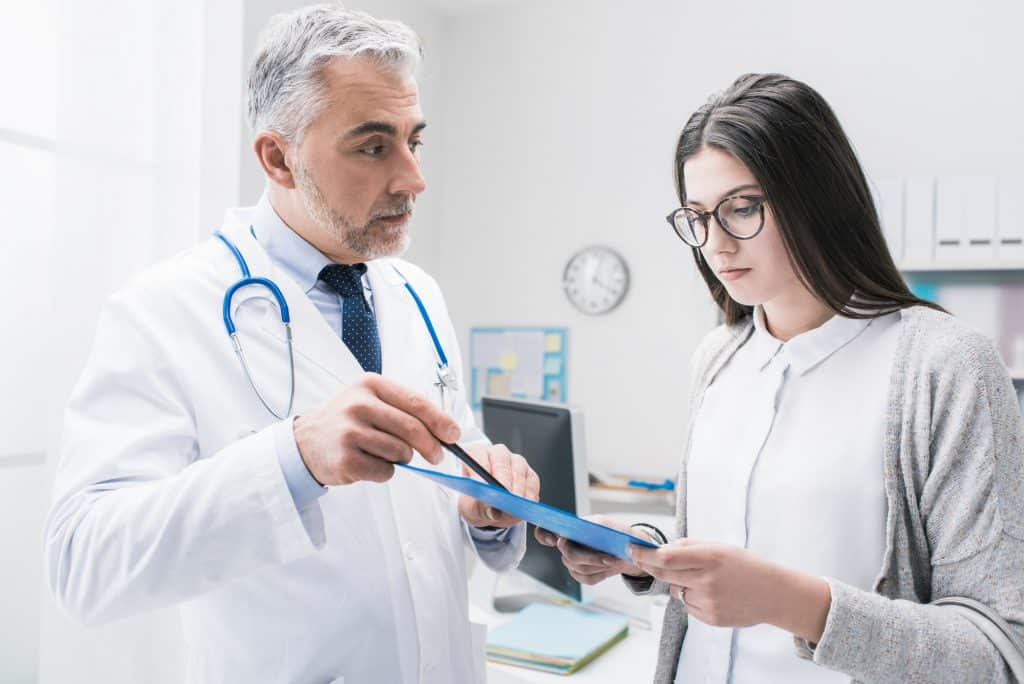 Doctor explaining medical test results to the patient, he is pointing on the clipboard with a pen, healthcare concept.