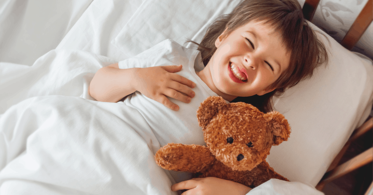 A toddler smiling while laying in the crib.
