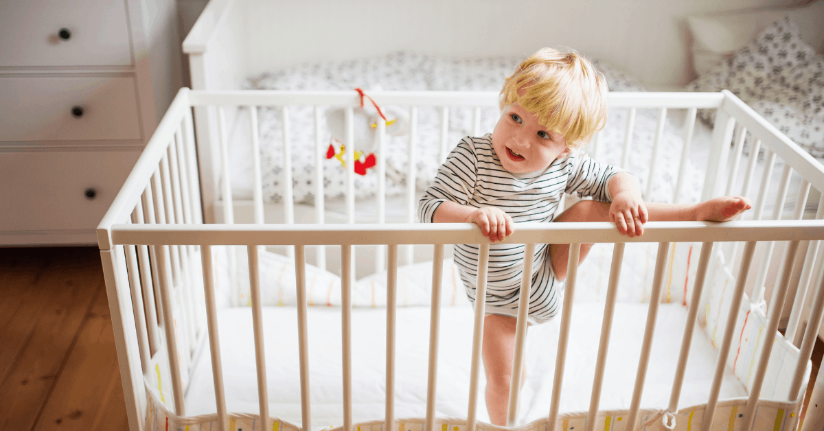 A toddler crawling out of his crib.